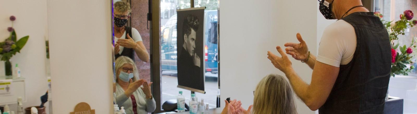 Der gehörlose Friseur Ralph unterhält sich mit einer Kundin