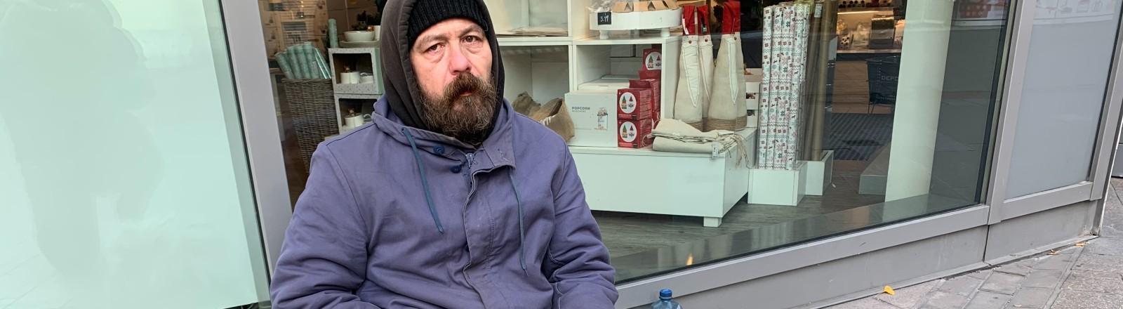 Der Obdachlose Willi sitzt auf der Straße angelehnt an ein Schaufenster