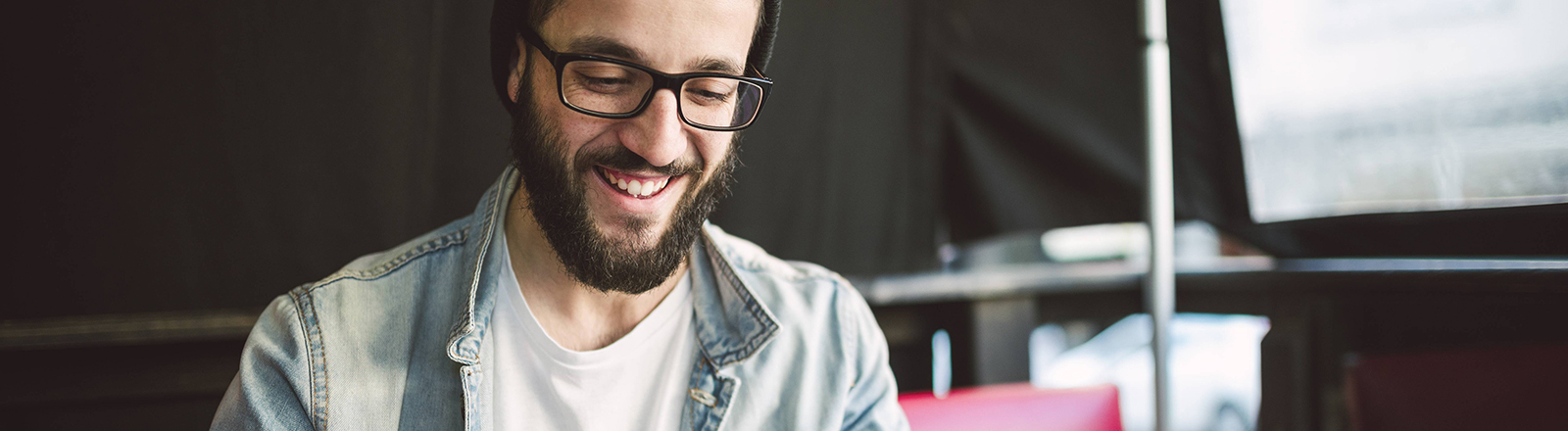 Ein Mann mit Brille und Mütze hält ein Tablet in der Hand und lächelt.