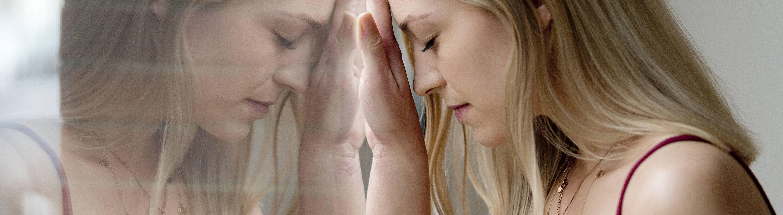 Eine Frau steht an einem Fenster und lehnt ihren Kopf gegen die Scheibe. In der Spiegelung ist sie ein zweites Mal zu sehen.