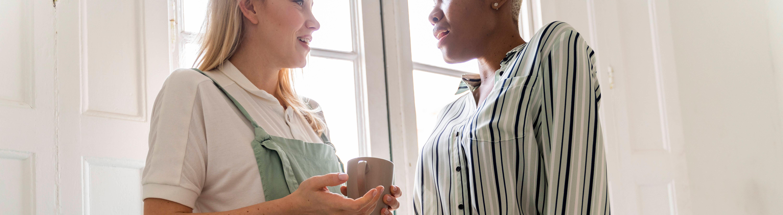 Zwei Frauen stehen sich gegenüber und unterhalten sich.
