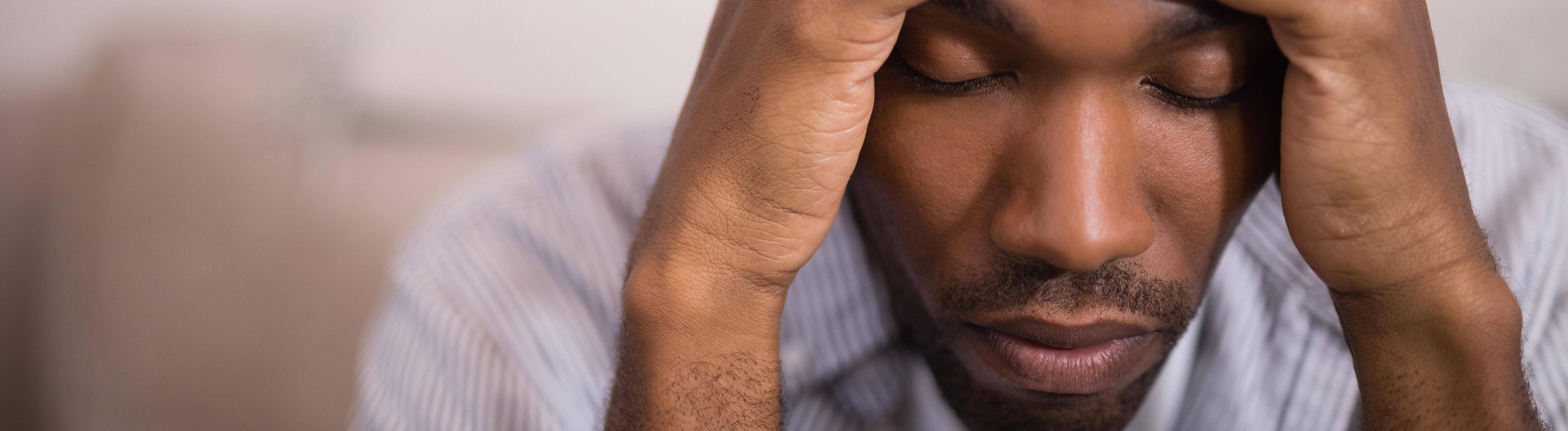 Mann sitzt und stützt seinen Kopf in seine Hände. Dabei hat er die Augen geschlossen.