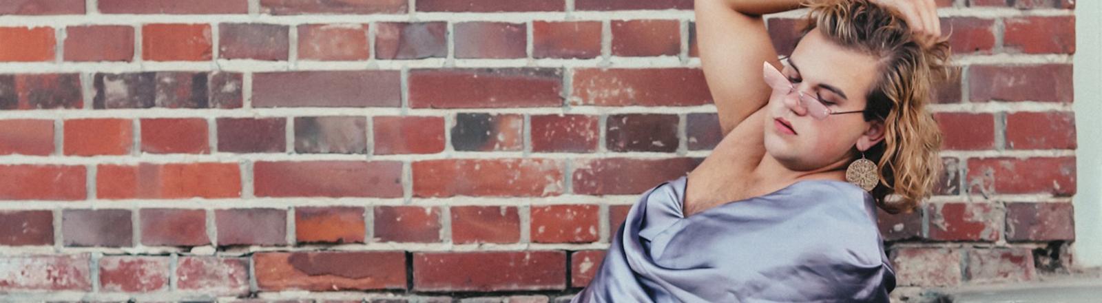 Eine Person sitzt in einem Kleid auf einer Treppe, lehnt sich zurück und fasst sich in die Haare.