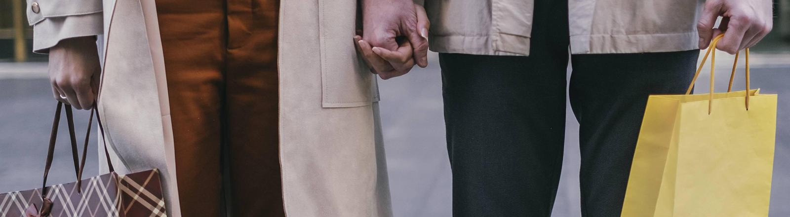 Zwei Menschen stehen nebeneinander und halten sich an den Händen. Sie haben jeweils eine Einkaufstüte in der Hand.