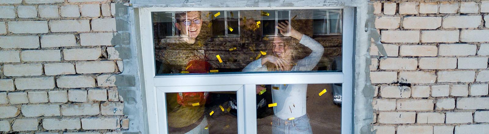 Zwei Menschen tanzen hinter einem verschlossenen Fenster.