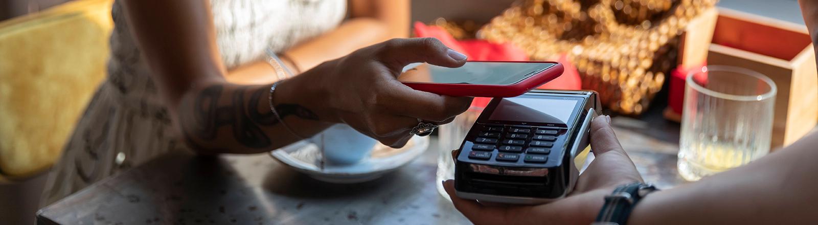 Eine Person sitzt an einem Tisch und hält ihr Handy über ein EC-Gerät, um kontaktlos zu bezahlen.
