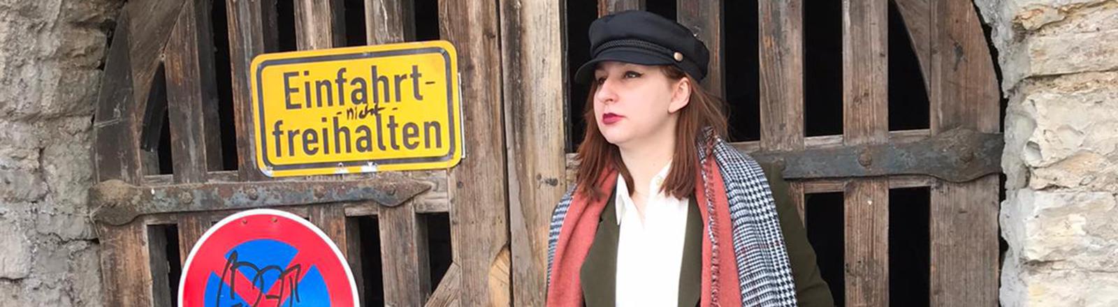 Eine Frau mit Hut steht vor einem Tor mit einem Schild.
