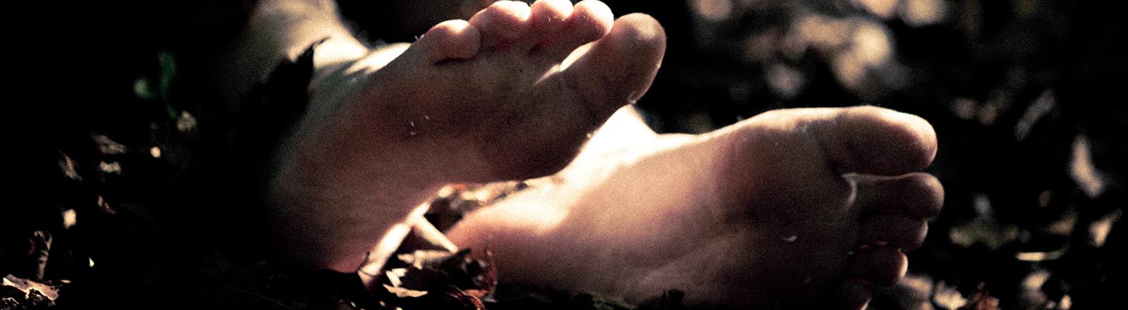 Zwei Füße liegen im Laub.