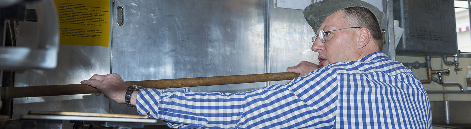 Der Bäcker Florian Bäcker schiebt mit einem langen Schieber ein Brot in den Ofen.