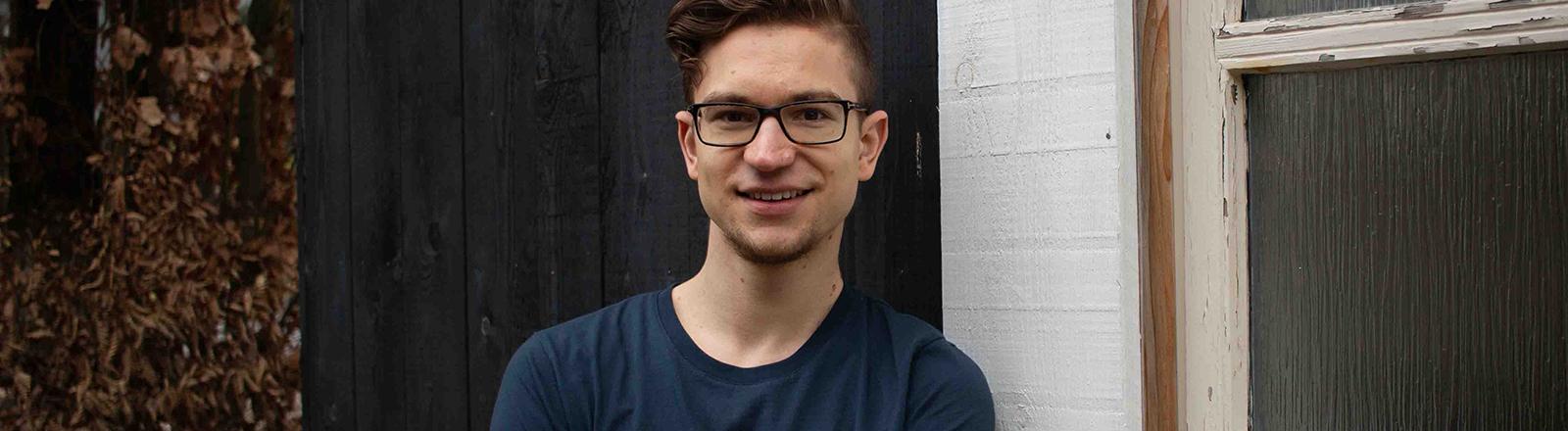 Ein Mann schaut in Kamera, er trägt ein T-Shirt und eine Brille.