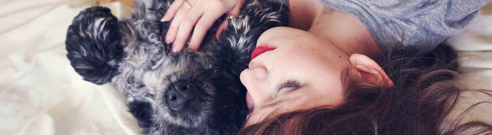 liegende Frau kuschelt mit einem schwarzen Hund