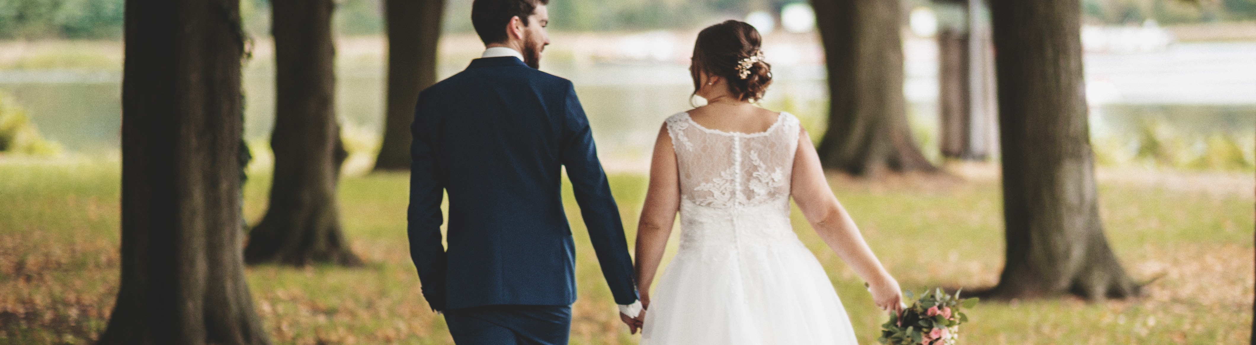 Hochzeitspaar von hinten, laufen unter Laubbäumen in Richtung See