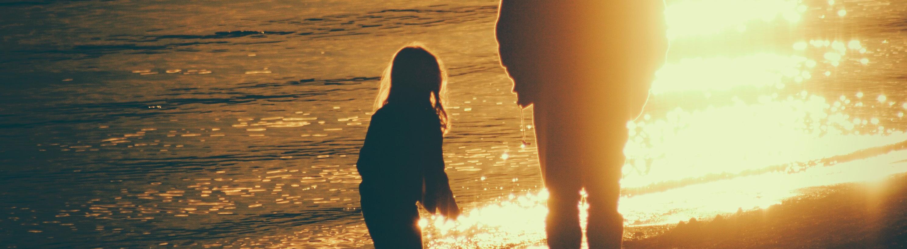 Erwachsener und Kind am Strand beim Sonnenuntergang