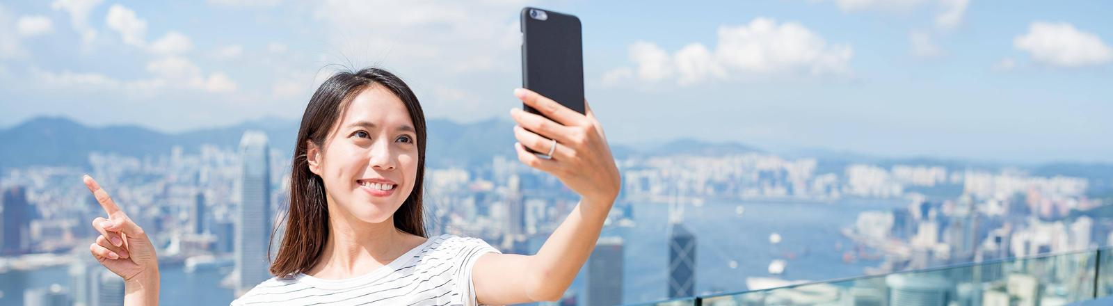 Eine junge Frau steht auf einer Dachterasse und macht ein Selfie vor einem Großstadtpanorama