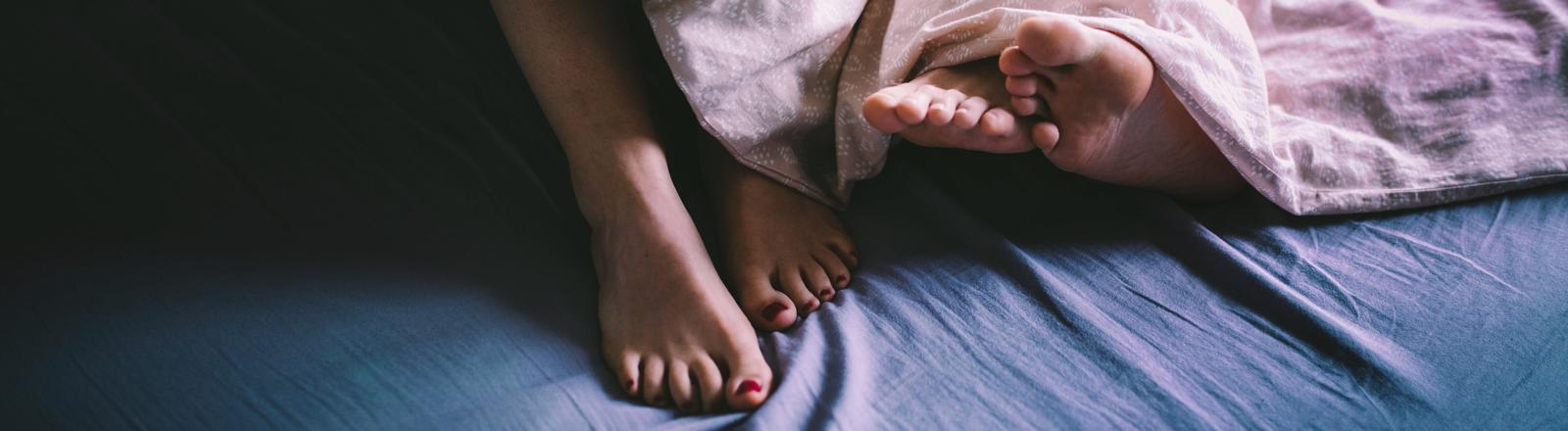 Füße eines Mannes und einer Frau lugen unter einer Bettdecke hervor
