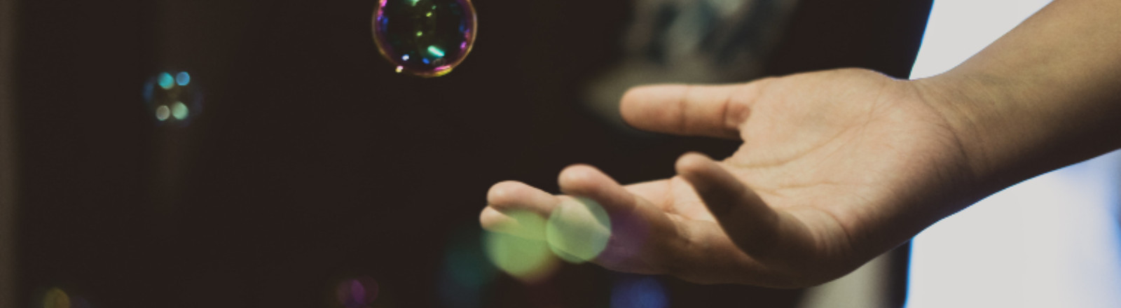 Frau hält Hand in Seifenblasen