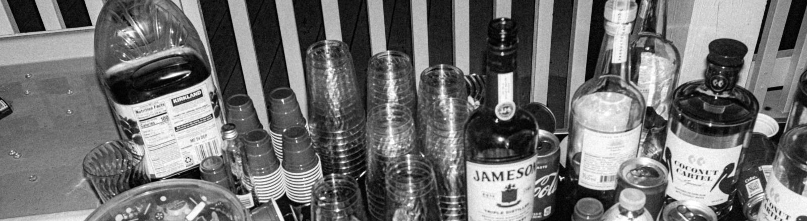 Ein Tischer voller leerer Alkholflaschen und Gläser