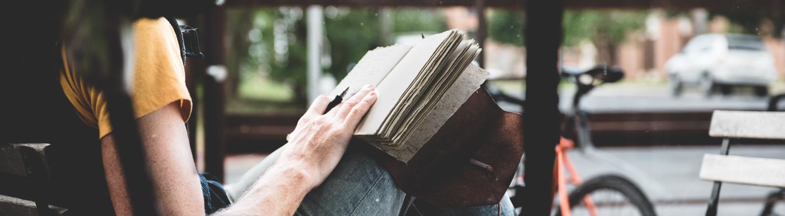 Mann sitzt auf einem Stuhl und schreibt Tagebuch.