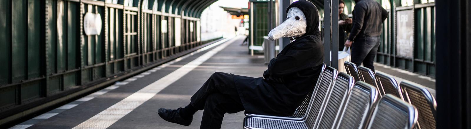 Mann mit Tiermaske sitzt auf einer Bank an einer Berliner S-Bahn-Station.