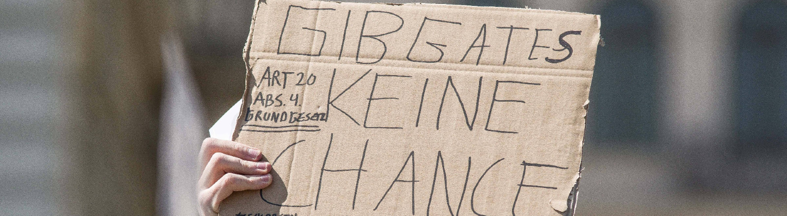 """Ein Demonstrant mit einem Plakat bei einer Hygiene-Demo mit der Aufschrift """"Gib Gates keine Chance"""""""