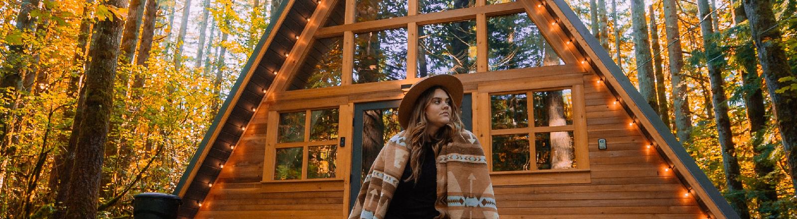 Eine Frau sitzt vor einem Holzhaus in Wald.