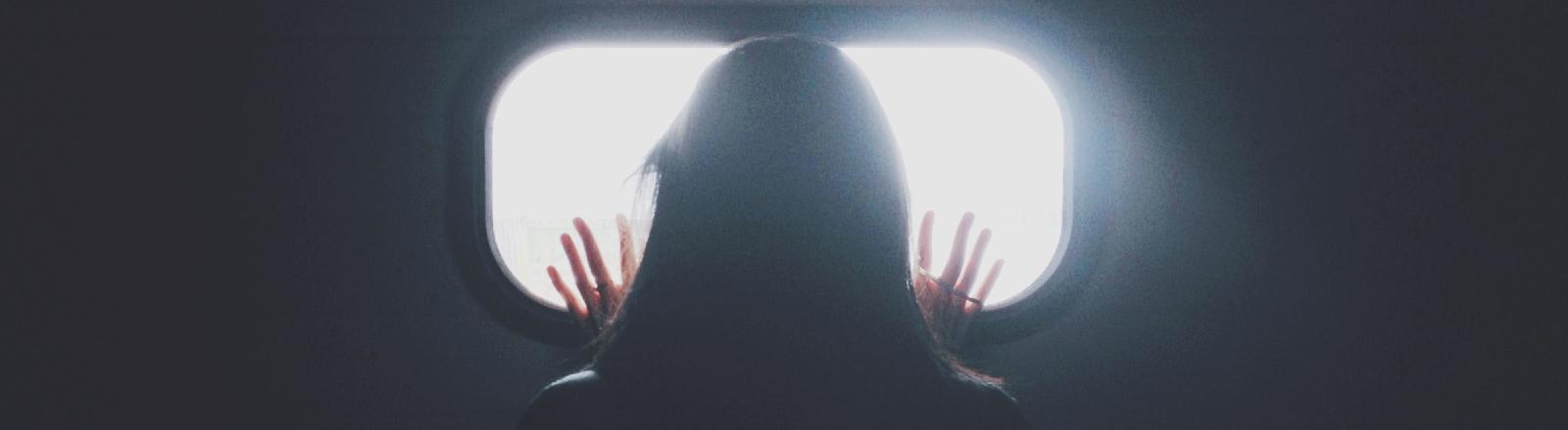 Eine Frau drückt die Hände gegen ein Fenster.