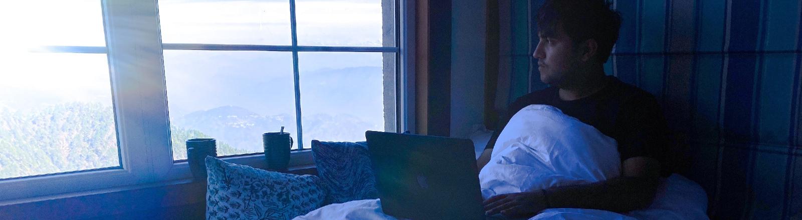 Ein Mann sitzt mit Notebook im Bett.