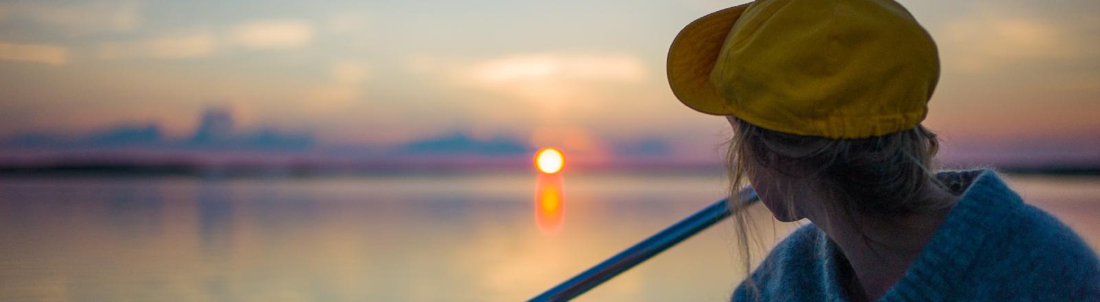 Eine Frau mit Basecap schaut in den Sonnenuntergang.