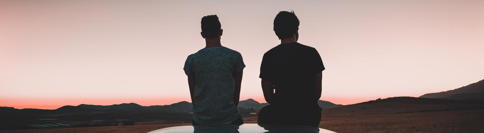 Zwei Männer sitzen auf einem Autodach.