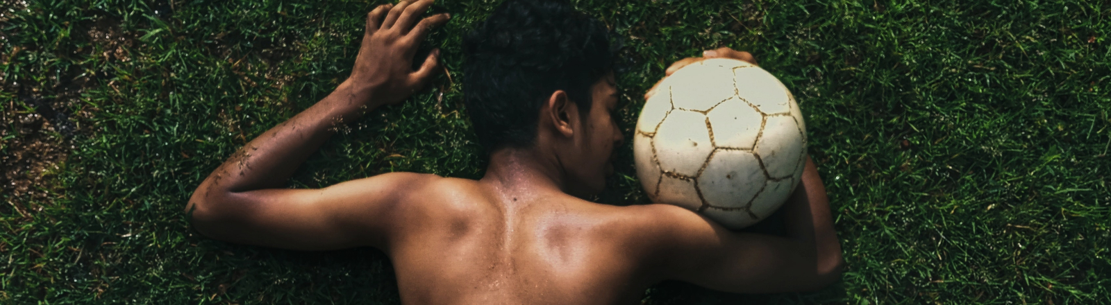 Ein junger Mann liegt neben einem Fußball.