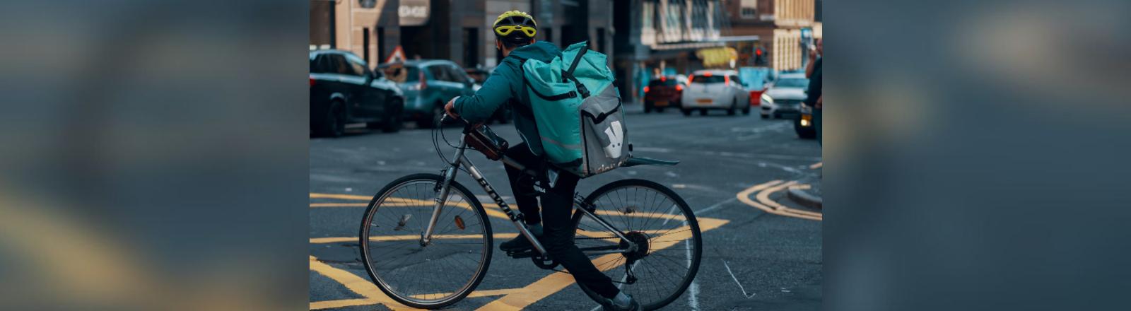 Ein Lieferdienstfahrer auf einem Rad.
