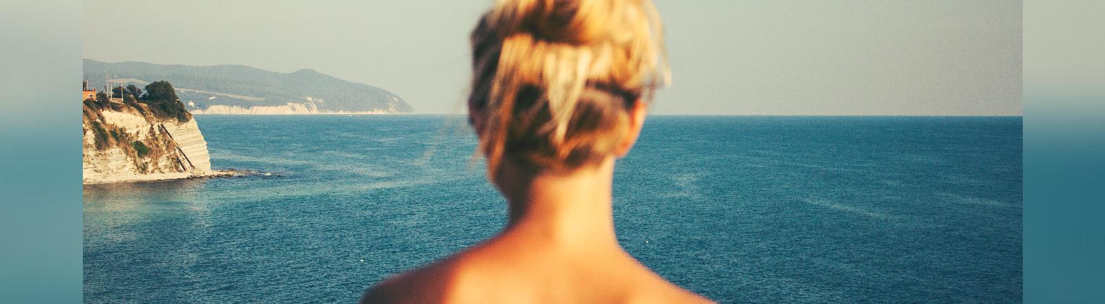 Eine Frau schaut auf das Meer.