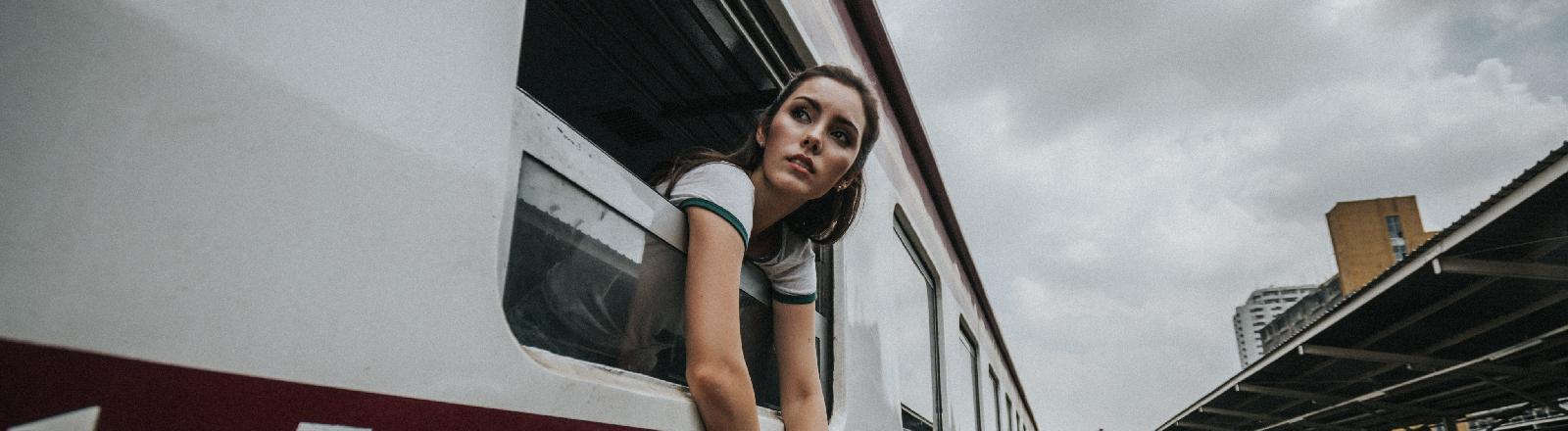 Eine Frau steckt Kopf und Arme aus einem Bahnfenster.