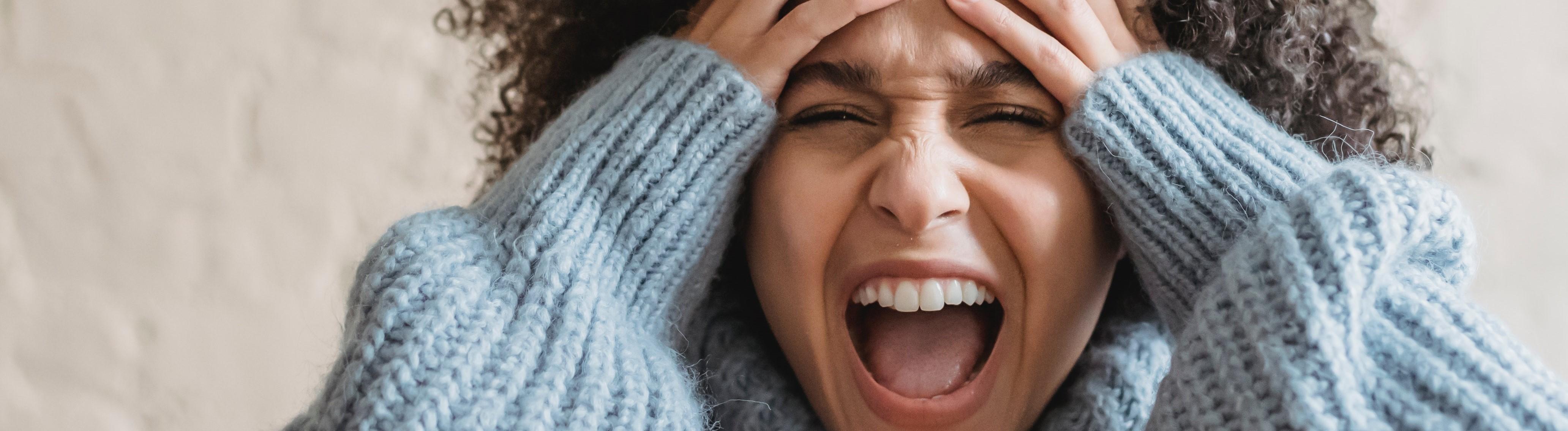 Frau hält Hände an Kopf und schreit
