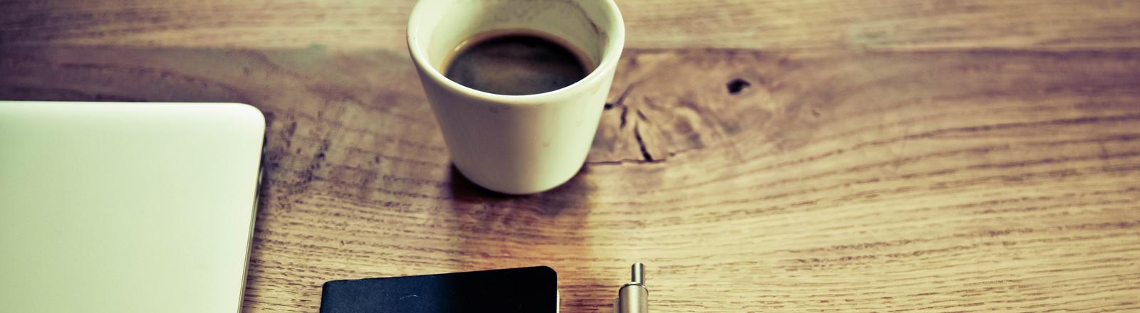 Laptop, Kaffetasse, Stift und Heft auf einem Holztisch