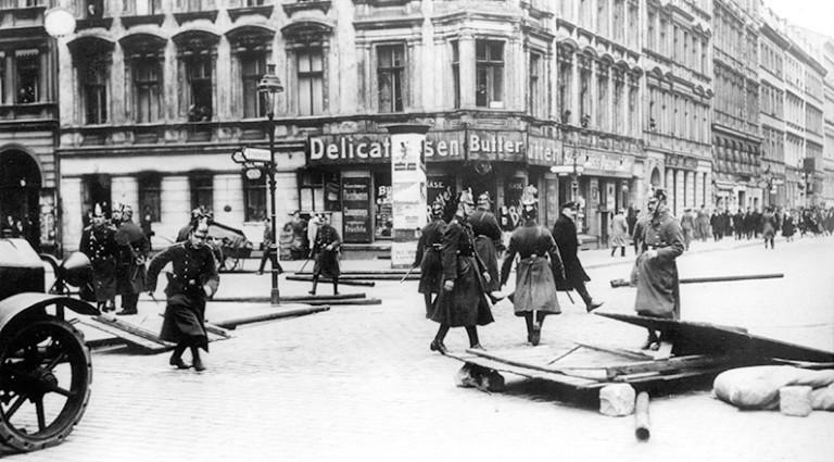 Polizisten entfernen eine von den Kommunisten errichtete Barrikade von einer Berliner Straße. Im Hintergrund eine auseinandergetriebene Gruppe von Demonstranten während der Maifeier 1929.