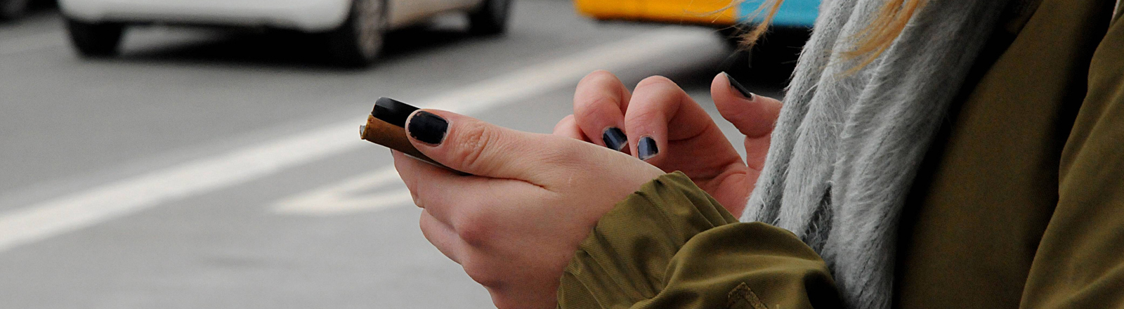 Frau mit Smartphone an Straße
