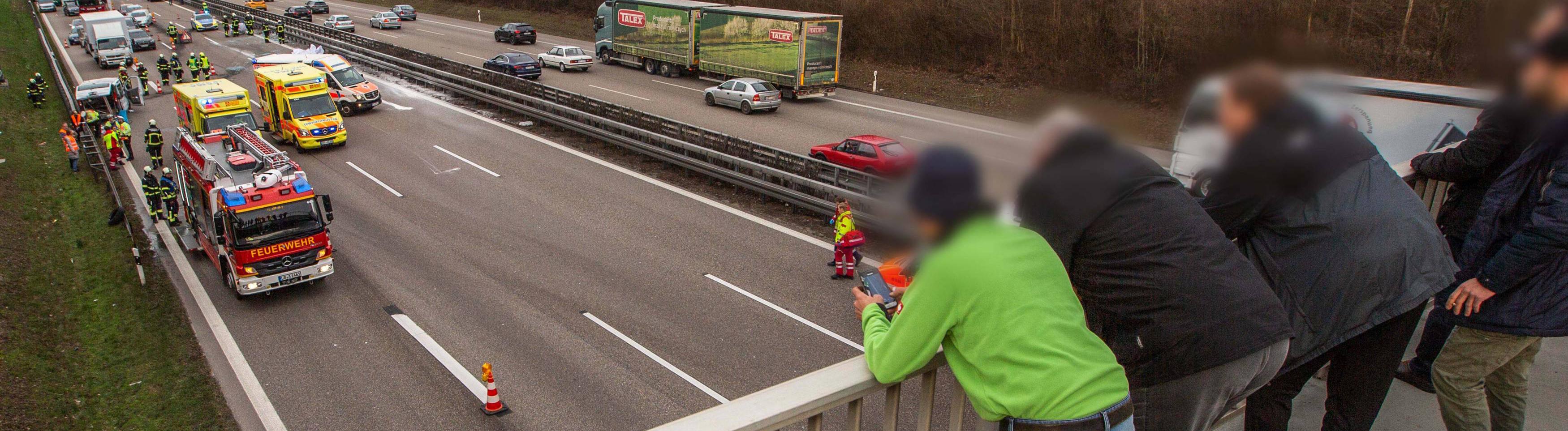 Schaulustige Gaffer auf einer Autobahnbrücke bei einem Verkehrsunfall