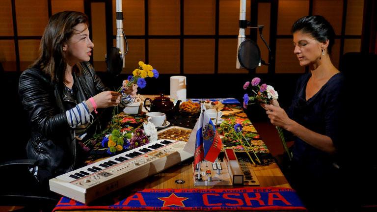 Videostill: Sahra Wagenknecht und Kat Kaufmann binden im Dlf Nova Studio Blumen