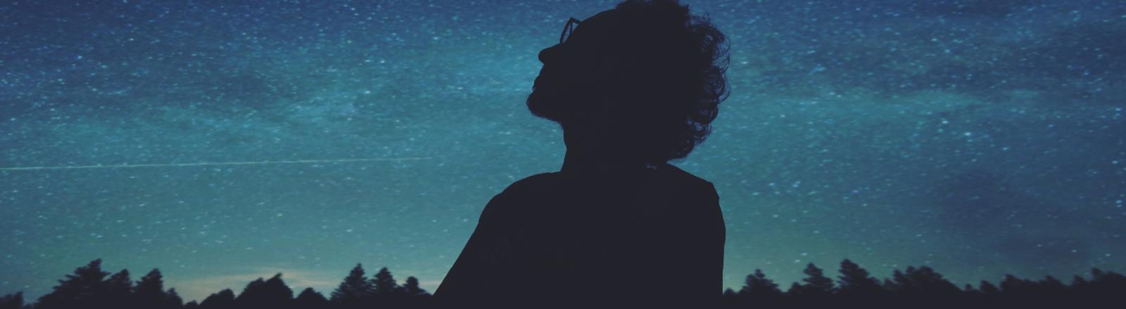 Ein Mann schaut in einen Sternenhimmel.