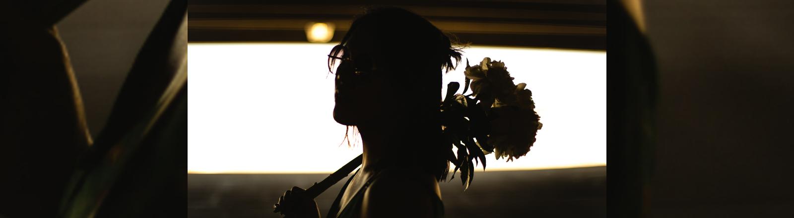 Frau mit Blumenstrauß über der Schulter.