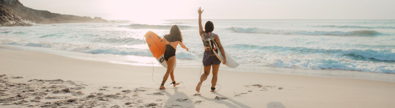Zwei Frauen laufen mit Surfbrettern auf das Meer zu.