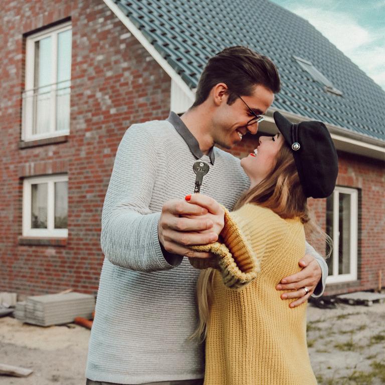 Junges Paar vor eigenem Haus