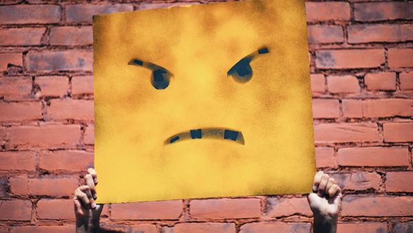 Zwei Hände halten ein Smiley-Plakat nach oben.