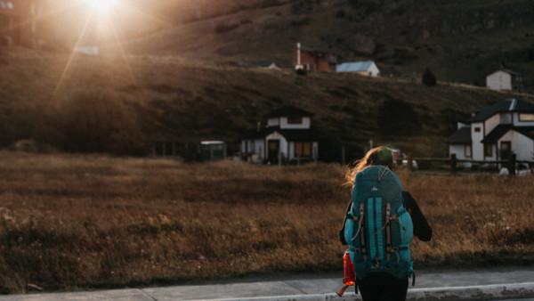 Mensch mit Rucksack vor Dorf