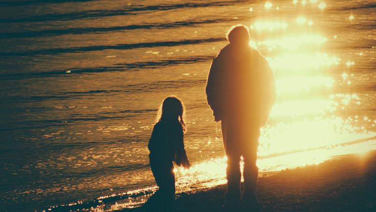 Erwachsener und Kind im Sonnenuntergang am Strand
