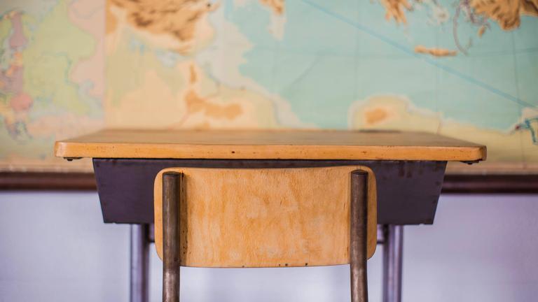Schulpult und Stuhl vor Weltkarte