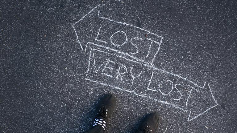 """Symbolbild Orientierungslosigkeit - Zwei Füße auf dem Asphalt, davor eine Kreidezeichnung zweier Pfeile mit der Aufschrift """"Lost"""" und """"Very Lost"""""""