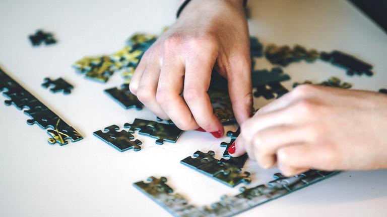 Ein Puzzle und zwei Hände