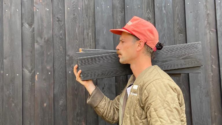 Felix steht mit Brettern über der Schulter vor einer Holzwand.